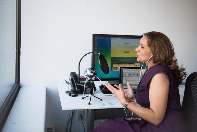 Woman wearing purple dress sitting on chair near window | podcast transcription | Preferred Transcriptions